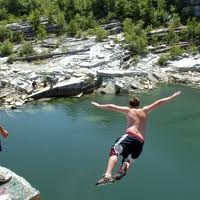 Teen flying through the air jumping into a quarry. An example of a Good Kid Taking Risks